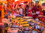 20 SEPTEMBER 2013 - BANGKOK, THAILAND:  Employees of the bars on Soi Cowboy in Bangkok buy food from a passing street food cart. Soi Cowboy is one of the notorious Entertainment Districts in Bangkok. Entertainment District has emerged as euphemism for red light district. Prostitution is officially illegal in Thailand but it is widely condoned. For western men, Soi Cowboy, along with Soi Nana and Patpong are among the most well known entertainment districts in Bangkok.      PHOTO BY JACK KURTZ