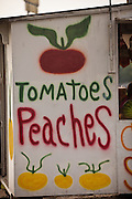 Roadside farm stand selling local produce including tomatoes and peaches