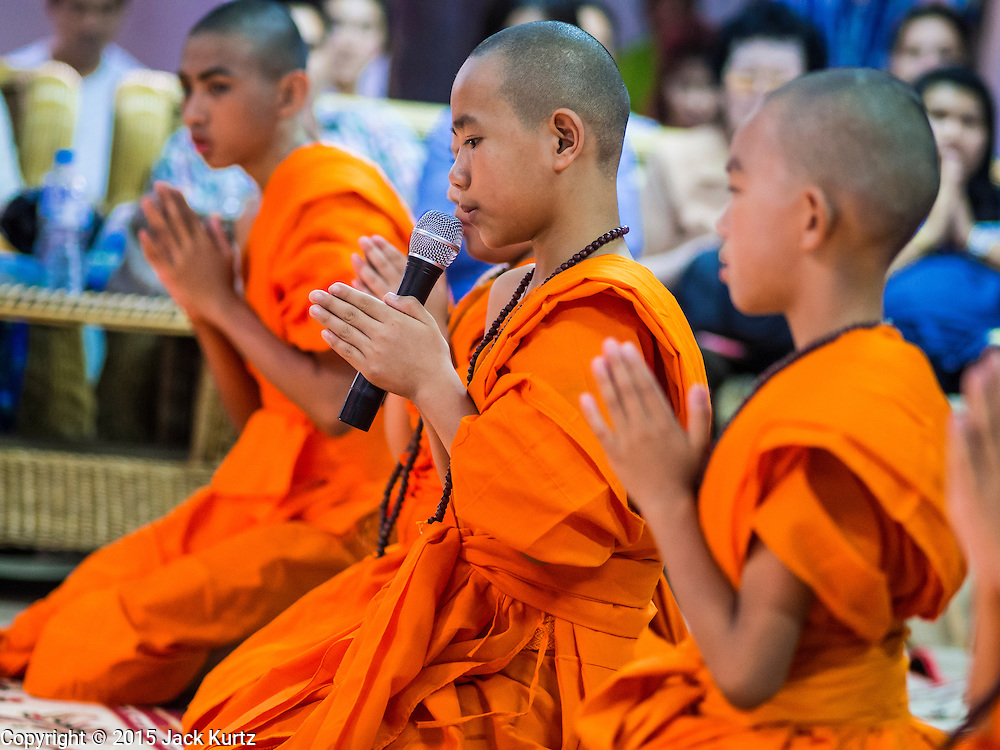 """06 APRIL 2015 - CHIANG MAI, CHIANG MAI, THAILAND: Newly ordained Buddhist novices participate in their first chanting service as monks during their ordination ceremony on the last day of the three day long Poi Song Long Festival in Chiang Mai. The Poi Sang Long Festival (also called Poy Sang Long) is an ordination ceremony for Tai (also and commonly called Shan, though they prefer Tai) boys in the Shan State of Myanmar (Burma) and in Shan communities in western Thailand. Most Tai boys go into the monastery as novice monks at some point between the ages of seven and fourteen. This year seven boys were ordained at the Poi Sang Long ceremony at Wat Pa Pao in Chiang Mai. Poy Song Long is Tai (Shan) for """"Festival of the Jewel (or Crystal) Sons.   PHOTO BY JACK KURTZ"""