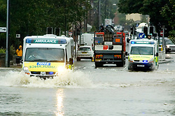 Torrential rain causes flooding and traffic chaos as ambulances try to make thier way through floodwater on The Common Ecclesfield Sheffield South Yorkshire.25 June 2007.Image COPYRIGHT Paul David Drabble.