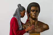 """Fredrika Newton, the widow of Black Panther Party's co-founder Huey Newton, touches his bust at The Artworks Foundry on Thursday, October 21, 2021, in Berkeley, Calif. Newton's bust was sculpted by artist Dana King. Oakland is installing its first ever permanent public art piece honoring the Black Panther Party, that was founded 55 years ago, in the city - a bronze sculpture of Huey Newton. Fredrika has been a longtime champion of the BPP's work and sees the statue as an important way to honor her late husband. At noon on Sunday, October 24, the Dr. Huey P. Newton memorial sculpture unveiling and dedication ceremony will be held at Mandela Parkway and Dr. Huey P. Newton Way in Oakland.<br /> <br /> """"He loved Oakland so much. So, now he's going back to the community that he loved,"""" Fredrika Newton said. """"It's kind of hard to land in the feelings when I'm really involved in so much planning, but in the quieter moments when I do get to access feelings, when I think of it, it brings me to tears, really. So, this weekend is, it's emotional because I have to let this beautiful image of him sit alone in a median strip and just pray that the community protects him with the same love and respect and reverence that he protected the community. So, it's a mixed bag. I feel on a very personal level that it's a really big step towards my own grief and healing, even after 32 years, it still exists because I never really let him go."""""""