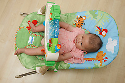Chinese baby lying in baby bouncer