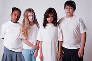 A group of children wearing white t-shirts looking sad, forlorn, lost, alone, and depressed.