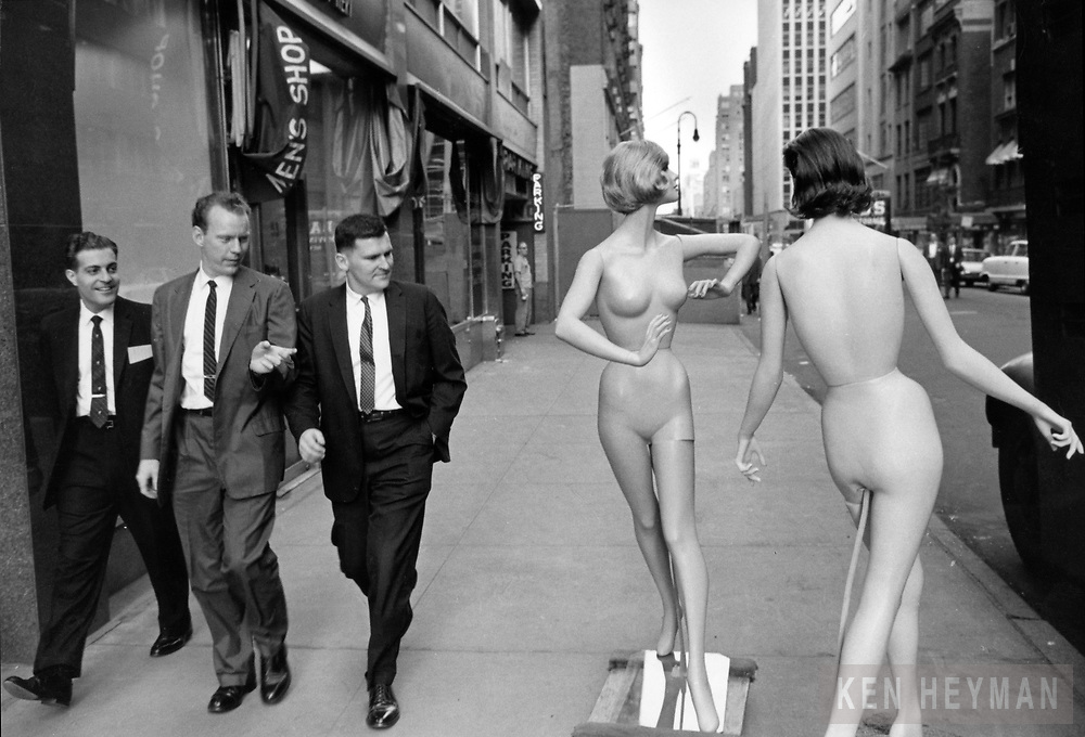Men on lunch break are amused by naked mannequins.