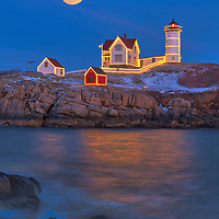 Full moon rise across the iconic Nubble Lighthouse with its Holidays Decoration taken at sunset in York, Maine. Loved watching this sunset burst into colors and capturing the Christmas Lights while the last light of the day created a beautiful sky across one of Maine's most iconic Christmas light scenes.<br />