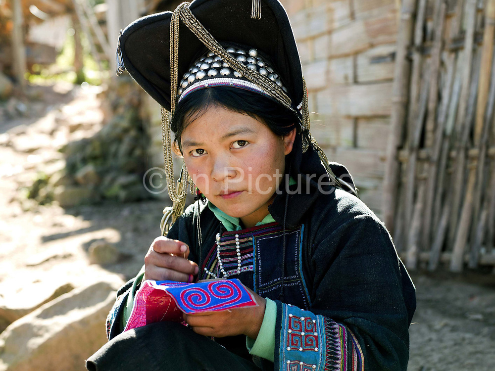Portrait of a 15 year old married Akha Nuquie ethnic minority woman sewing outside her home in Ban Pang Hok Kao village, Phongsaly Province, Lao PDR.  She is wearing the Akha Nuquie traditional costume made from hand woven cotton and dyed with indigo and decoarated with hand embroidery typical of the Akha Nuquie sub-group; the high headdress distinguishes her as a married women. One of the most ethnically diverse countries in Southeast Asia, Laos has 49 officially recognised ethnic groups although there are many more self-identified and sub groups. These groups are distinguished by their own customs, beliefs and rituals. Details down to the embroidery on a shirt, the colour of the trim and the type of skirt all help signify the wearer's ethnic and clan affiliations.