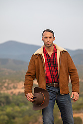 cowboy holding his cowboy hat outdoors on a mountain top
