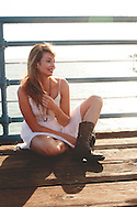 A pretty twenty-something wearing a sun dress and boots.