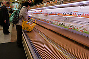 Shoppers empty shelves at a super market, panic buying due to shortage fears after a magnitude 9 earthquake and large tsunami hit the Tohoku region of north east Japan  on March 11th killing nearly 20,000 people and causing massive destruction along the whole coast, and a melt-down at the Fukushima Daichi nuclear power station. Tokyo, Japan Monday, March 14th 2011