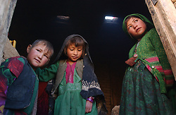 ANBAR SOMUCH, AFGHANISTAN, AUGUST 1, 2002: Rozima, 10, right, plays with Shukria, 7,  and Subira, 5, left,  in Anbar Somuch, Afghanistan, August 1, 2002. More than 100 families have returned to their village after the fall of the Taliban and they are rushing to rebuild their homes before the brutal winter sets in. (Photo by Ami Vitale)