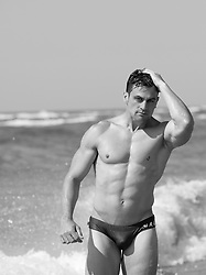 muscular man in a small bikini at the ocean