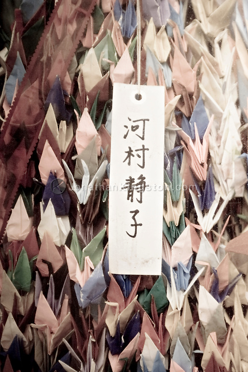 Folded paper cranes at the Hiroshima Peace Memorial Park, Hiroshima, Japan.  The paper cranes are a symbol of the hope for world peace and are inspired by the story of Sadako Sasaki, a girl who died from leukemia caused by the nuclear blast in Hiroshima.  Sadako Sasaki believed that if she folded one thousand cranes, she would be granted a wish.  After Sadako's death, a statue of her holding a golden crane was unveiled in Hiroshima.  At the foot of the statue a plaque reads, This is our cry.  This is our prayer.  Peace in the world.  Once the paper cranes are displayed, they are pulped and recycled into bookmarks, notebooks and other souvenirs which are sold in the Rest House in Hiroshima.