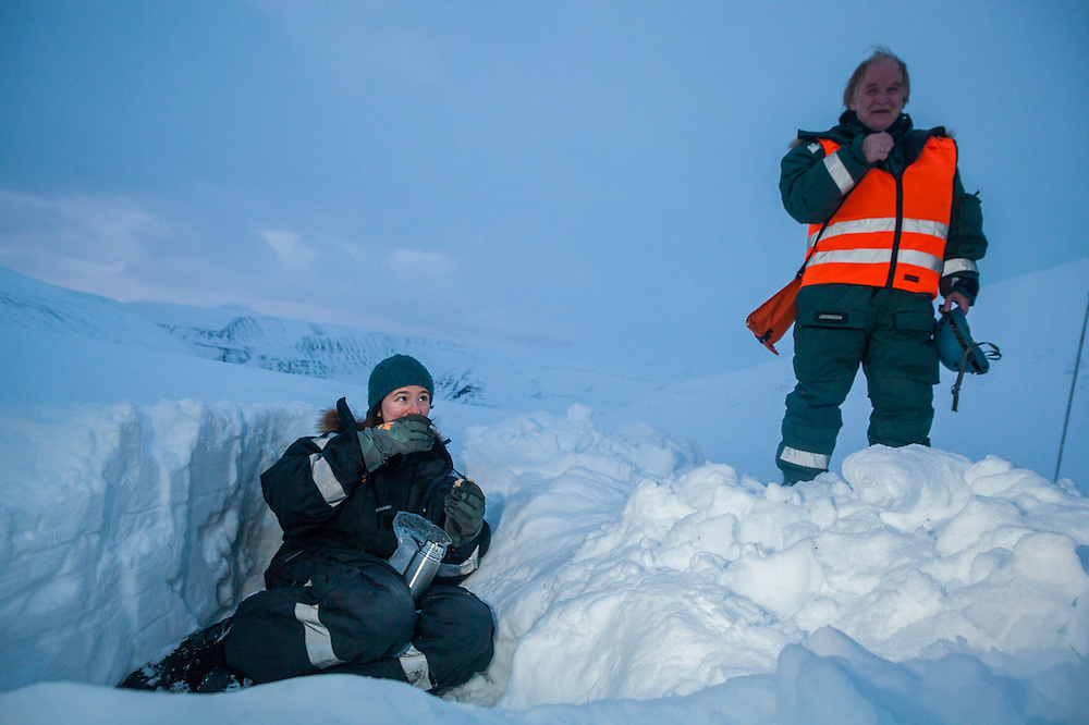 UNIS professor Doug Benn (right) and his student Kiya Riverman relax after digging snow study pits in Bolterdalen, Svalbard.