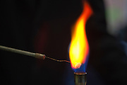 A secondry school pupil in the science lab testing chemicals in the bunsen burner.
