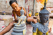08 MAY 2013 - BANGKOK, THAILAND:  A worker finishes Buddha statues in a workshop on Thanon Bamrung Muang. Th Bamrung Muang is one of the first paved roads in Bangkok. Many shops that sell Buddhist religious supplies and statuary are located on Bumrang Muang.        PHOTO BY JACK KURTZ