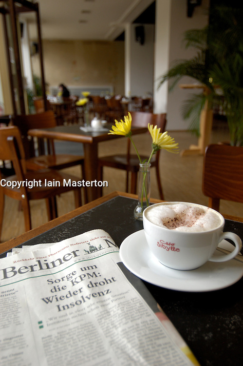 Detail of coffee and newspaper in famous Cafe Sybille on historic Karl Marx Allee in Berlin Germany