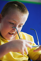 Pupil with physical disability in a special school cleaning his glasses,