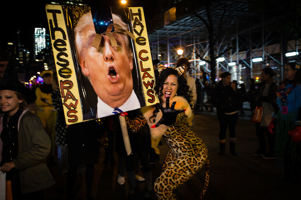 "New York, NY - 31 October 2016. Skater, performance artist and political activist Marni Halasa wears a cat suit and carries a sign with a mutilated photo of Donald Trump, the sign captioned ""These paws have claws."""