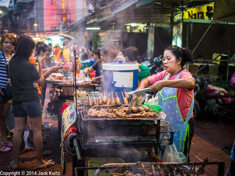 25 OCTOBER 2014 - BANGKOK, THAILAND: A vendor grills Thai and Chinese sausages at a street food stall near Yaowarat Road in Bangkok. Yaowarat Road is the center of the Bangkok Chinatown neighborhood and is famous for the street food. Most of the food stalls open after sunset.     PHOTO BY JACK KURTZ