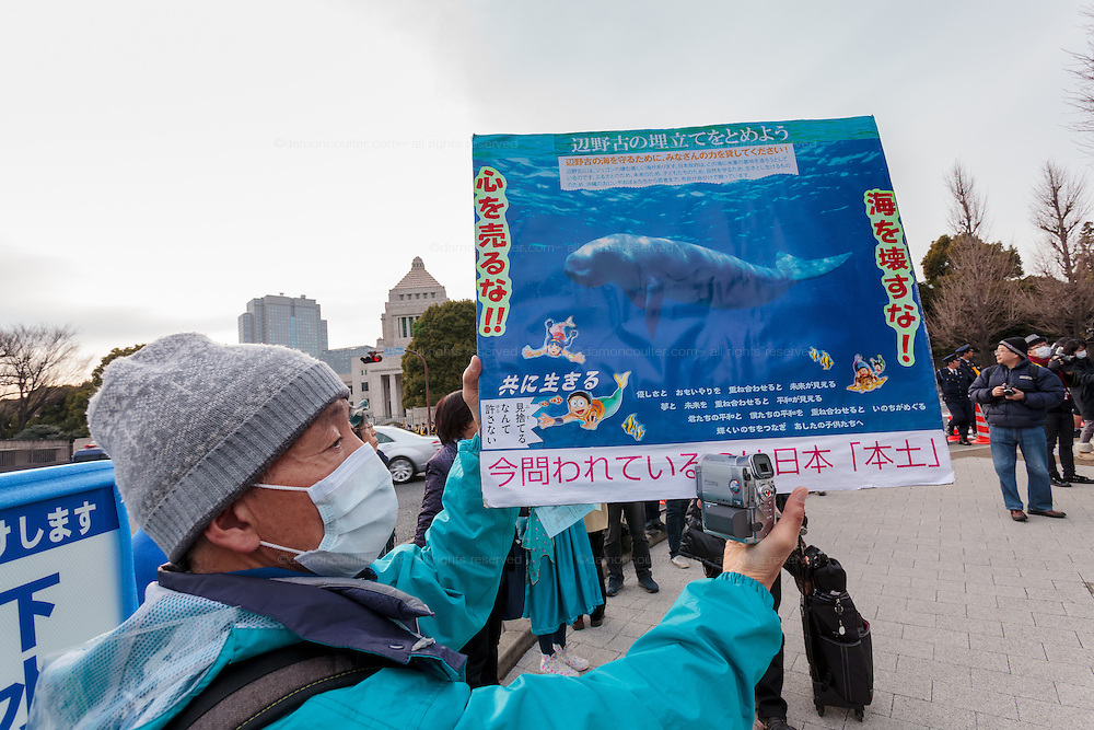 A man holds a poster about the threat to the rare dugong marine mammal at a rally to protest the construction of a new US military base at Henoko in Okinawa outside the Japanese National Diet building, Nagatacho, Tokyo, Japan Sunday January 25th 2015. Organisers say 7,000 people joined the protest forming a human chain around the Assembly Building.