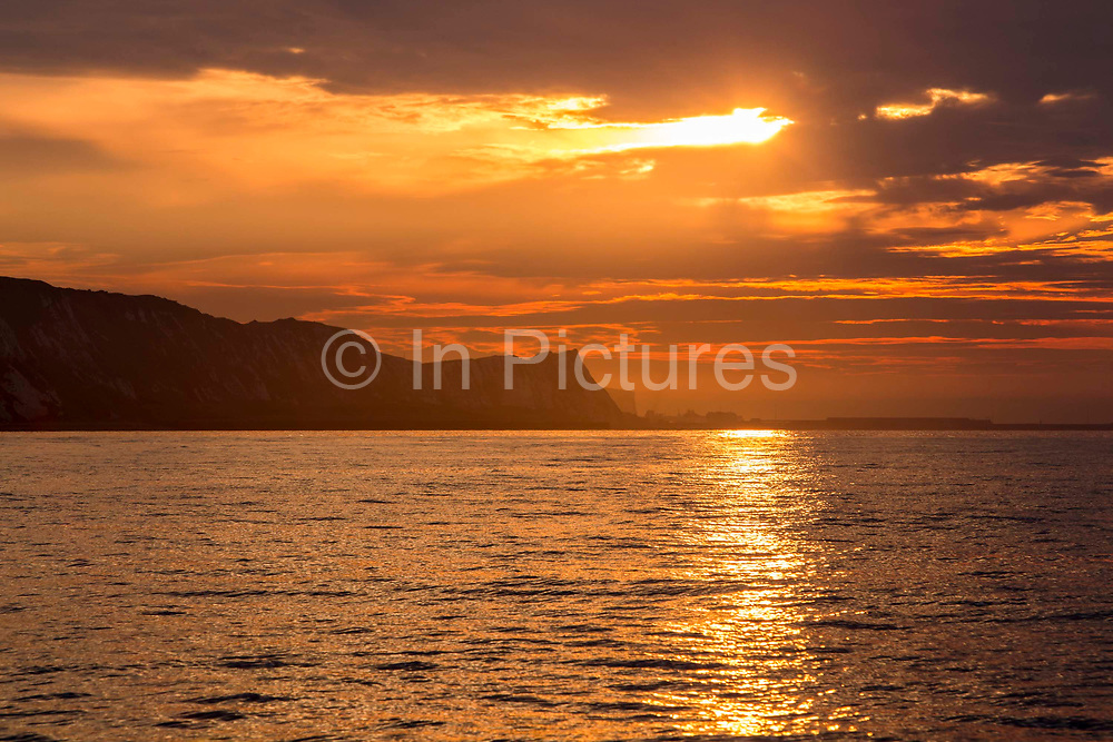 The sun rises over The White Cliffs of Dover and breaks through the clouds in the sky and the sunlight reflects along the calm sea water photographed from a boat in The English Channel off the coast of Folkestone Harbour, Kent, England, United Kingdom.  The Folkestone Harbour Arm and lighthouse can be see in front of the cliffs.