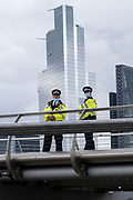 Police wearing face masks look on from Millennuim Bridge towards Extinction Rebellion activists on 6th September 2020 in London, United Kingdom. It has been reported that several police officers have tested positive for Covid-19 after attending XR demonstrations recently. Extinction Rebellion is a climate change group started in 2018 and has gained a huge following of people committed to peaceful protests. These protests are highlighting that the government is not doing enough to avoid catastrophic climate change and to demand the government take radical action to save the planet.