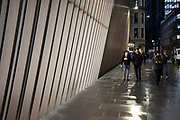 People interact with the modern architectural detailing on a wall outside a new office buiding in the City of London on 26th November 2019 in London, England, United Kingdom. More and more of the city is being redeveloped with buildings becoming incresingly tall.