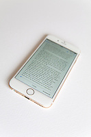 Gold and white Apple iPhone 6 with an ebook on screen against a white background