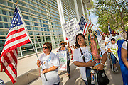 """19 JULY 2012 - PHOENIX, AZ:  People march around the US Courthouse on the first day of a class action lawsuit, Melendres v. Arpaio in Phoenix Thursday. The suit, brought by the ACLU and MALDEF in federal court against Maricopa County Sheriff Joe Arpaio, alleges a wide spread pattern of racial profiling during Arpaio's """"crime suppression sweeps"""" that targeted undocumented immigrants. U.S. District Judge Murray Snow granted the case class action status opening it up to all Latinos stopped by Maricopa County Sheriff's Office deputies during the crime sweeps. The case is being heard in Judge Snow's court.  PHOTO BY JACK KURTZ"""