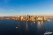 Aerial view of lower Manhattan, New York City, from New York Harbor, showing the sun glinting off One World Trade Center, photographed at sunset from a helicopter.