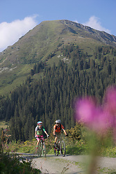 Two mountain bikers riding on dirt road through forest, Zillertal, Tyrol, Austria