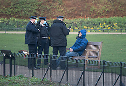 © Licensed to London News Pictures. 09/01/2021. London, UK. Three police officers wearing face masks question a man sitting on a bench in St James's Park in central London. Metropolitan police have said that people who flout lockdown restrictions and gather in groups without wearing masks can expect to be fined under a new crackdown. Photo credit: Ben Cawthra/LNP