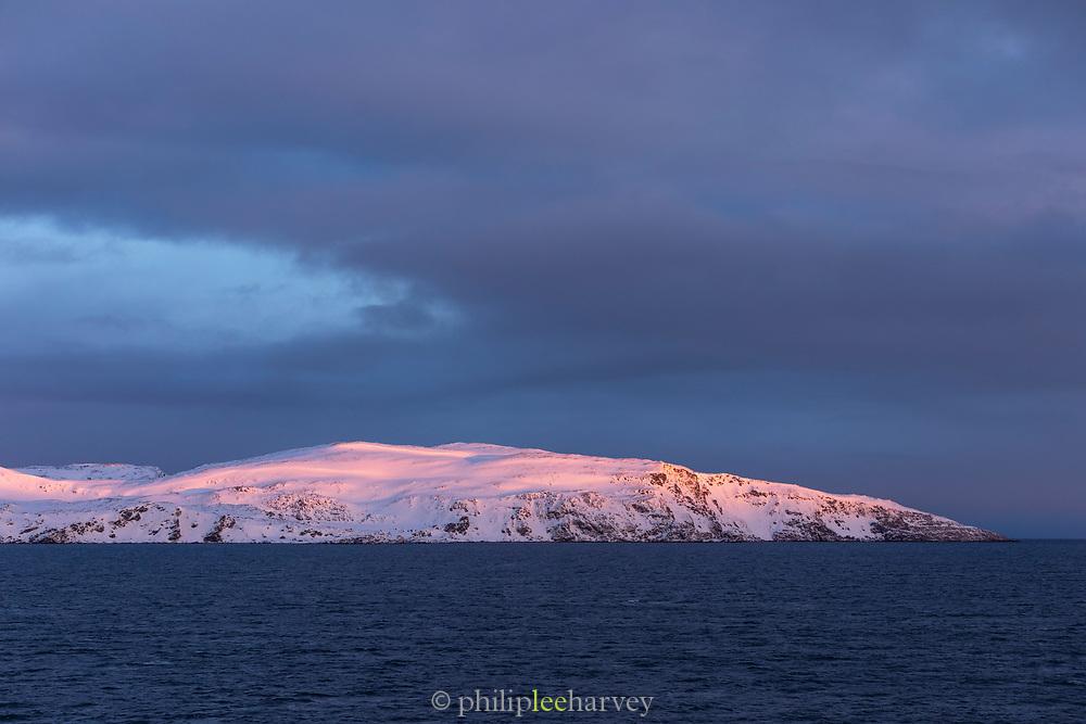 Scenic winter landscape against moody sky at sunrise, Havoysund, Norway