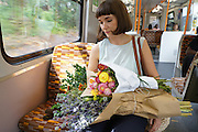 Traveling local, Terri Chandler takes her flowers by London local traim to a nearby restaurant.<br /><br />Terri Chandler of Worm London, based in Stoke Newington. Part of a recent 'start up'. She and her partner set up last year after taking diplomas in flower arrangement. They run a local business with local British Flowers which they buy from New Covent Garden Market. They work for restaurants, weddings and functions.<br /><br />British local flowers, grown nearby, count for around 10% of the UK market, traveling less than a tenth of their foreign counterparts which are often flown in from abroad. Nearly 90% of the flowers sold in the UK are actually imported, and many travel over 3000 miles. Local flower farms help biodiversity, providing food and habitat to a huge variety of wildlife, insects including butterflies, bugs, and bees. Often local flower farmers prefer to grow organic rather than using pesticides. British flowers bloom all the year around, even in the depths of winter, and there are local flower farms throughout the country.<br /><br />Many people like the idea of the just picked from the garden look, and come to flower farms throughout Britain to pick their own for weddings, parties and garden fetes. Others come for the joy of a day out in the countryside with their family. Often a bride and her family will come to pick the flowers for her own wedding, some even plant the seeds earlier in the year.