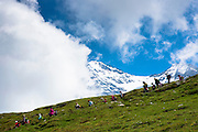 Japanese tourists on walking trail by the Eiger and Jungfrau mountains in the Swiss Alps, Bernese Oberland, Switzerland