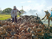 Women removing fired ceramic pots and barbeques in Duc Binh, a Hindu Cham village in Binh Thuan province, Central Vietnam. Firing is done in an open pit with temperatures going up to 800 degree Celcius. The pots are arranged together and covered with layers of rice straw, which is set on fire.