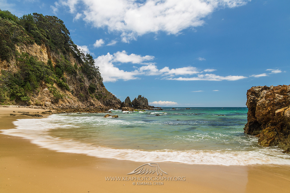 A beautiful arc formed by the incoming tide connects the rocky northern shore of Opito Bay, Coromandel Peninsula, New Zealand.