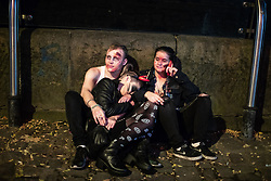 © Licensed to London News Pictures . 28/10/2018. Manchester, UK. Three people sit huddled together on the ground on Canal Street in Manchester City Centre . Revellers on a night out , many in fancy dress , on the weekend before Halloween . Photo credit: Joel Goodman/LNP