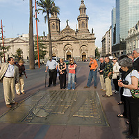 A tour guide in the Plaza de Armas, below the Metroplitan Cathedral, explains an old, bronze map of downtown Santiago