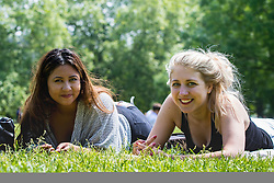 Green Park, London, June 6th 2016. Friends Aly Iman and Amanda Reg enjoy the warm weather in Green Park as London basks in glorious summer sunshine with highs of 24º expected.
