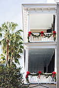 Christmas roping decorates the balcony piazzas of a historic Charleston Single house with palm trees on Meeting Street in Charleston, SC.