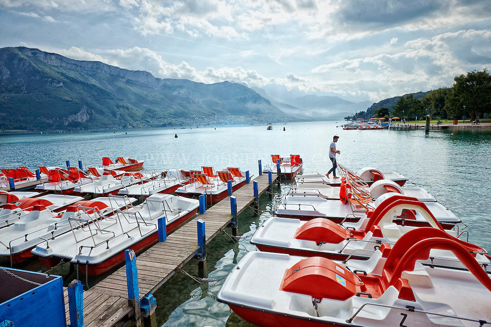 A gorgeous view of paddle boats, the misty French Alps, and Lake Annecy settled beneath a cozy, cloudy sky.