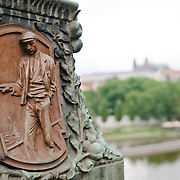 Communist plaque of a worker on a bridge in Prague with Prague Castle in the distance