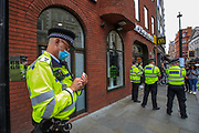 A Policeman takes notes as he observes an Extinction Rebellion climate protest near Covent Garden in central London on Monday, Aug 23, 2021. This is a two week planned of action against new fossil fuel investments. XR protestors are aiming to occupy parts of central London for two weeks from Monday, aiming to force the Government to halt all new investment in fossil fuels. (VX Photo/ Vudi Xhymshiti)