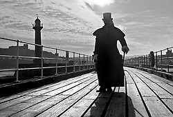 © Licensed to London News Pictures.01/11/15<br /> Whitby, UK. <br /> <br /> A man wearing gothic clothing stands on the pier as hundreds of visitors attend the Whitby Goth weekend in Whitby, North Yorkshire. The event began in 1994 to celebrate goth culture and music and takes place twice each year. <br /> Thousands of extravagantly dressed people attend the popular event wearing Steampunk, Cybergoth, Romanticism, Victoriana and other clothing as they take part in the celebration of Goth culture. <br /> <br /> Note to Editors - Picture shot on Kodak Tri X 400ISO film.<br /> Photo credit : Ian Forsyth/LNP