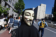 An anti nuclear protester wearing a Guy Fawkes mask on the back of his head during a protest march in Tokyo, Japan Sunday June 2nd 2013