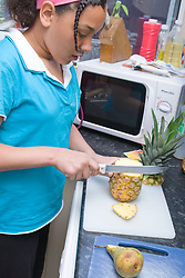 Teenaged girl slicing up a pineapple in the kitchen at home,
