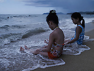Two Vietnamese girls play at the shore edge in Hoi An, Vietnam, Southeast Asia