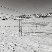 SuperDARN antenna array getting buried by the incessant drifting snow, South Pole Station in the distance.