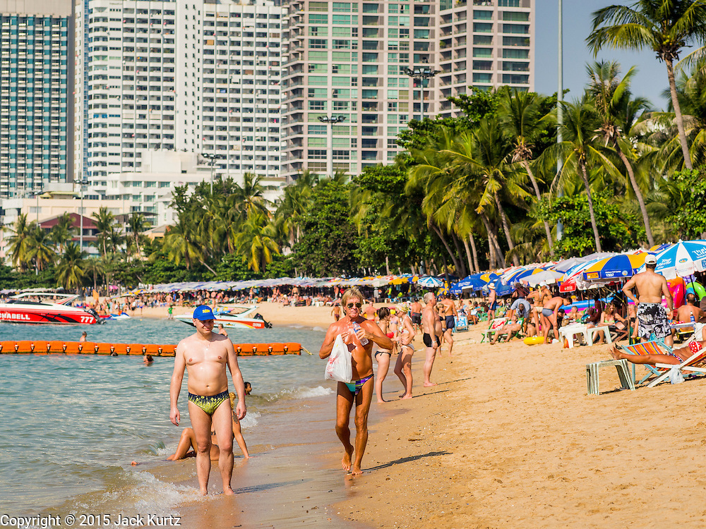 06 JANUARY 2015 - PATTAYA, CHONBURI, THAILAND:  Tourists on Pattaya beach. The Thai government has announced plans to clean up Pattaya beach, one of the most famous beaches in Thailand. Pattaya is about 2.5 hours from Bangkok. They plan to reduce the number of umbrella and chaise lounge vendors on the beach and regulate the personal watercraft and parasailing vendors on the beach. The government has already cleaned up beaches on Phuket island and Hua Hin.   PHOTO BY JACK KURTZ